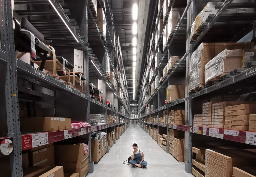 person-sitting-on-ground-between-brown-cardboard-boxes-2701434